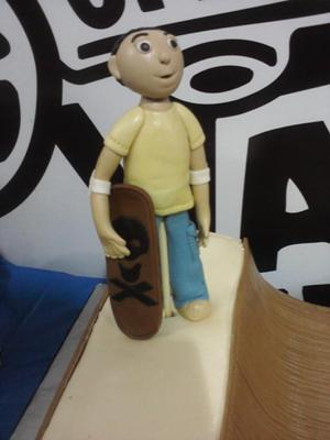 Half pipe shaped cake with a human figurine topper