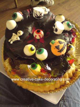 Chocolate covered cake decorated with fondant eyeballs and pumpkin toppers