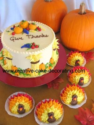 Round white cake with pumpkin deco and cupcakes decorated in turkey design