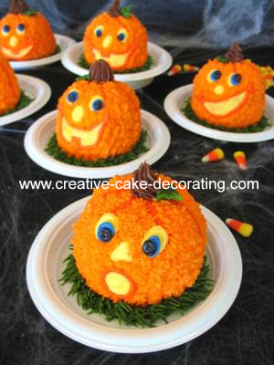 Sphere shaped cakes decorated to look like pumpkins with facial features