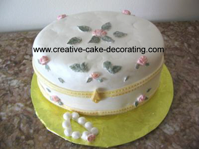 A white cake in the shape of a jewelry box with pink floral design
