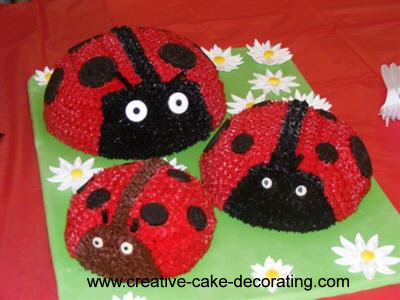 3 half bowl shaped ladybug cakes on a green cake board decorated with white daisies.
