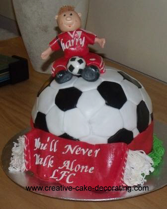 A round football shaped cake with a human figurine topper. Cake is in Liverpool football theme.