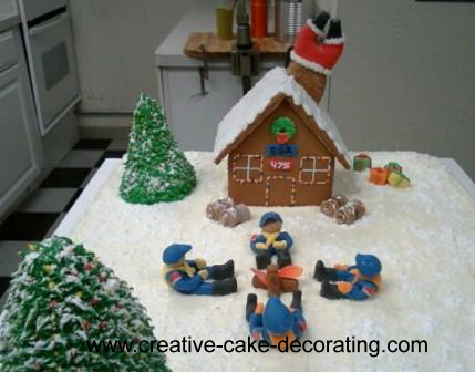 A rectangle cake with an edible house structure on top along with green trees and 4 boy scout figurines.