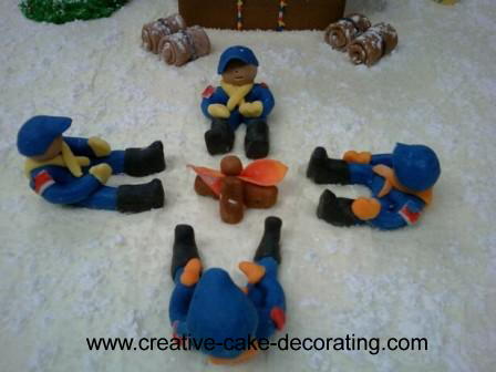 4 boy scout figurines on a cake