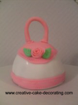 Mini handbag cake in white and pin with a tiny pink rose deco.