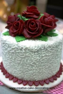 Round white cake in white cornelli lace and maroon roses topper