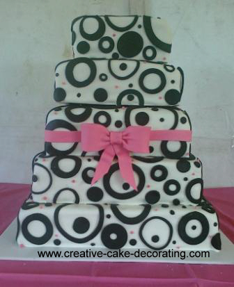 5 tier square cake with pink fondant ribbon and black circle patterns