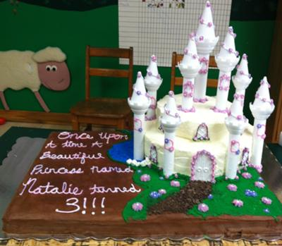 White, 2 tier castle cake with white turrets and floral decoration.
