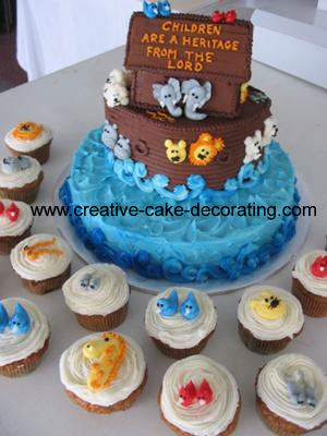 A two tier cake with brown and blue icing. Top of the cake is a boat shaped topper with animal faces all around the sides of the middle tier and the top.