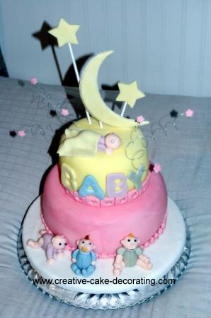 A 2 tier cake in yellow and pink and a large crescent moon topper.
