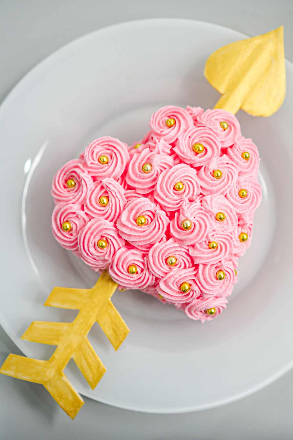 A pink buttercream rossette frosted heart shaped cake with a gold gum paste arrow through it.