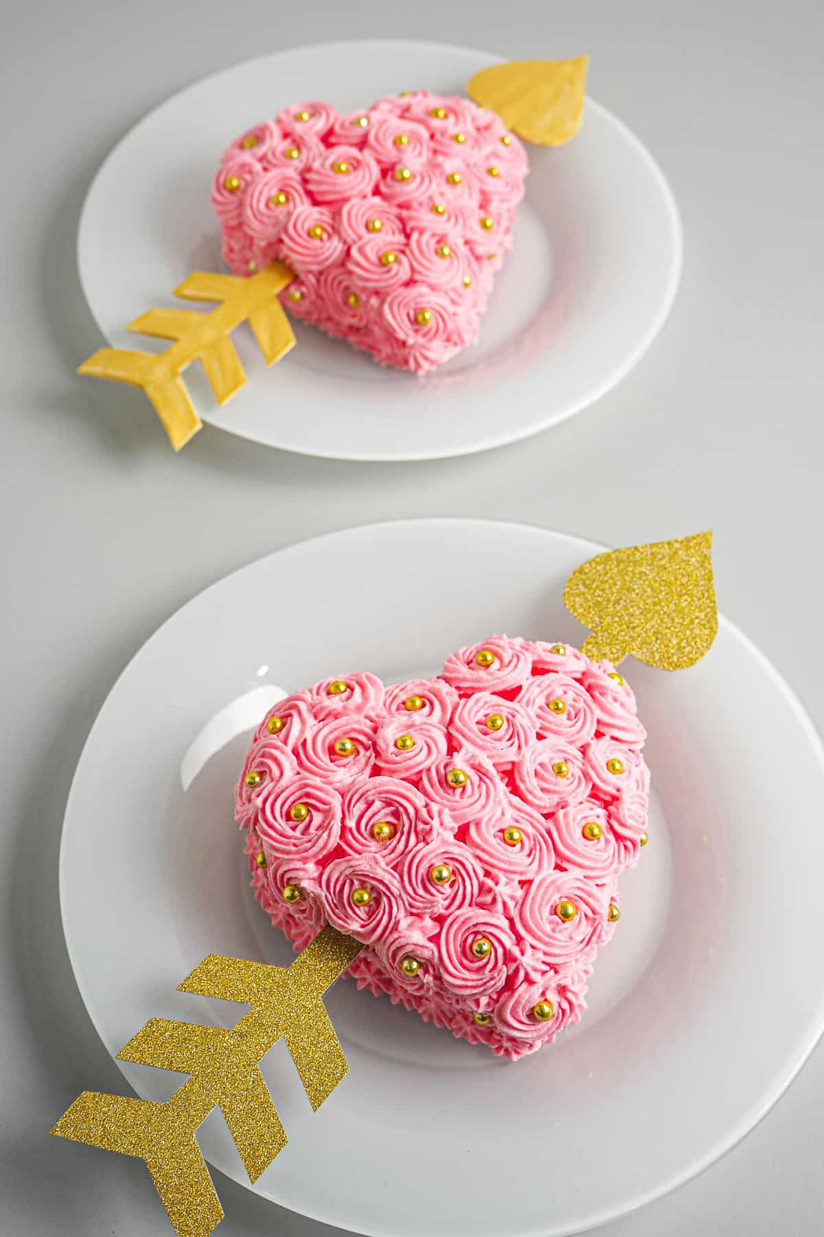 A pink buttercream rossette frosted heart shaped cake with a gold paper arrow through it.