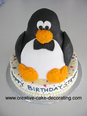 A 3d penguin cake in black, white and yellow. Penguin is on a round bottom tier cake.
