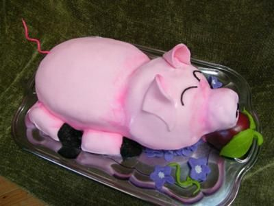 A pink 3D pig shaped cake on a silver tray.