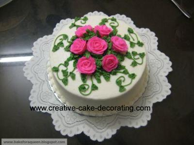 White cake with pink buttercream toppers in the center and green leaves and scrolls on the sides