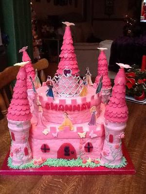 2 tier pink castle cake with princess images on the second tier.