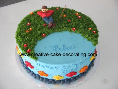 A round cake with half blue icing and half green icing. Cake is topped with a human figurine sitting in a relaxed position.