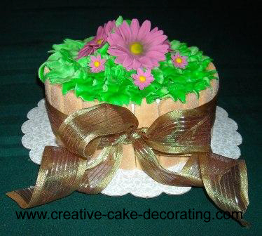A round cake decorated in green and purple gerberas