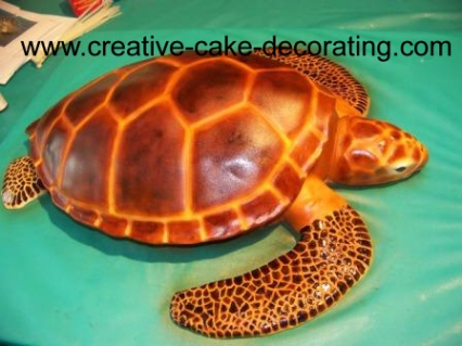 A 3d turtle cake in brown on a green cake board