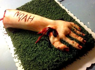 Cake in the shape of a severed arm with blood oozing