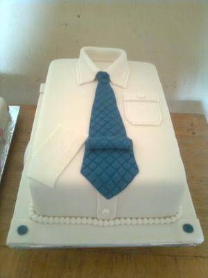 A rectangle cake decorated with white and blue fondant to look like a folded shirt with a blue tie on.