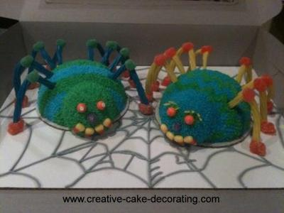 2 half bowl shaped spider cakes in green and blue icing. One spider with blue legs and the other with orange and yellow legs.