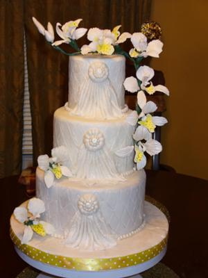 3 tier white cake with white and yellow orchids