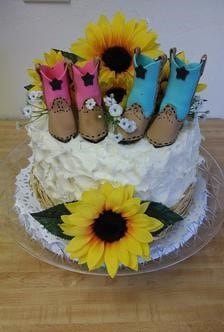 Single tier cake decorated with a large silk sunflower and 2 pairs of boots toppers.