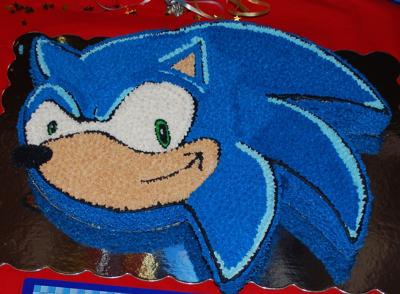 Cake in the shape of Sonic the Hedgehog face iced in blue.