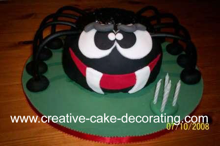 A spider shaped cake in black, on a green cake board. Spider has sharp fangs and big round eyes