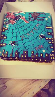 A blue rectangle cake with black spider web and icing spiders