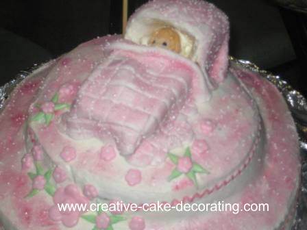 A pink and white round cake with a baby in a cradle topper