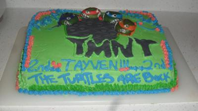 A rectangle cake with green icing and teenage mutant ninja turtles design