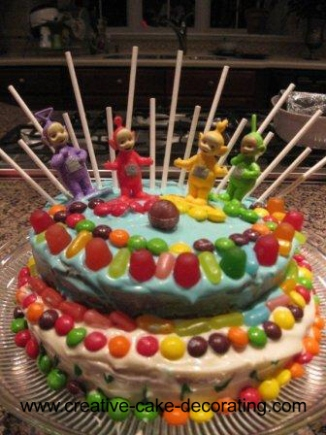 2 tier cake with teletubbies toppers and bright colorful candies.