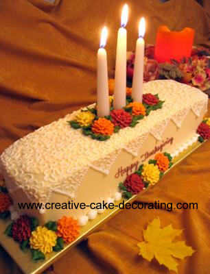 A rectangle cake with cornelli lace icing and flowers in fall colors