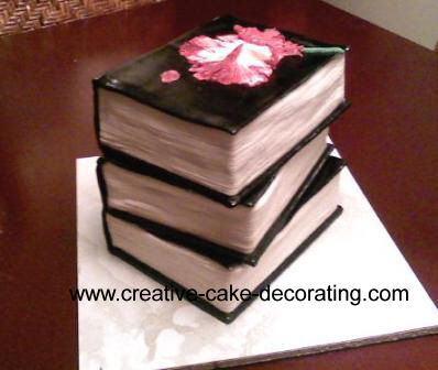 A stack of 3 books cake with black cover and white pages.