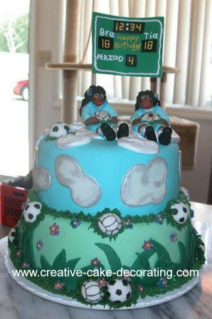Blue and green two tier cake with 2 fondant figurine toppers
