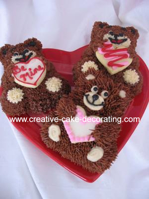 3 mini bears cakes on a red heart shaped board.