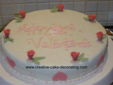 Round white cake with pink roses and green leaves deco.