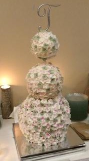 A 3 tiered wedding cake with ball shaped cakes decorated in white and green flowers.