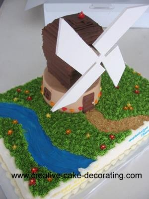 A windmill shaped cake on a bottom rectangle cake.