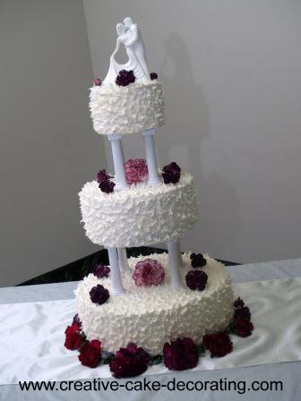 3 tiered white cake on pillars with spikes icing and red flowers