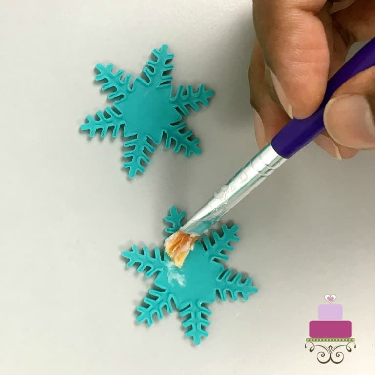 Applying shortening to cut out snowflake fondant pieces