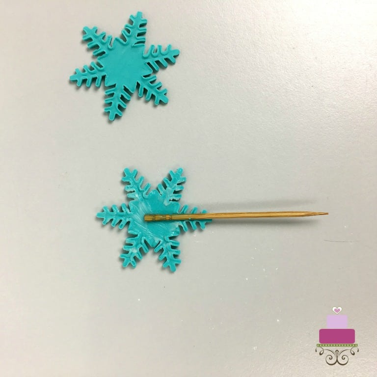 A toothpick on a piece of snowflake fondant cut out. Next to it is a fondant snowflake cut out