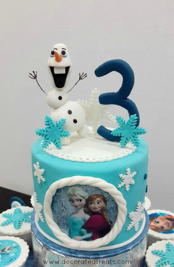 3D Olaf cake topper on a light blue round cake decorated with Frozen theme