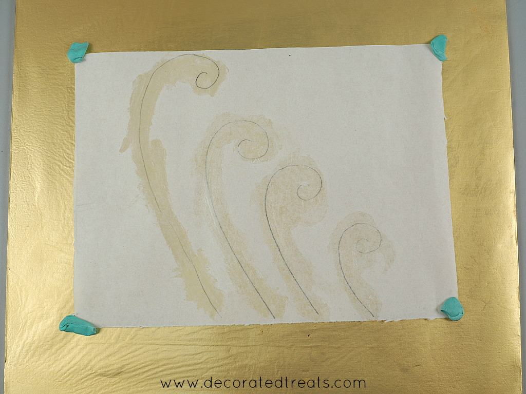 Fondant waves paper template on a gold cake board