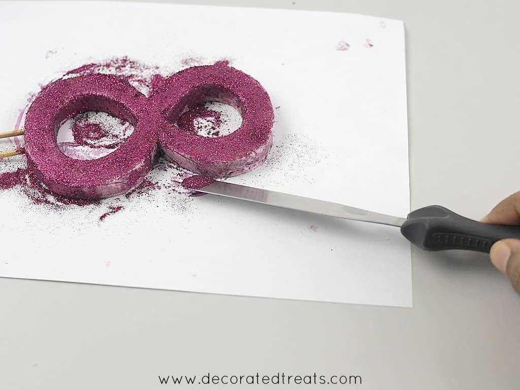 Using a palette knife to attach purple glitter onto a number 8 shape