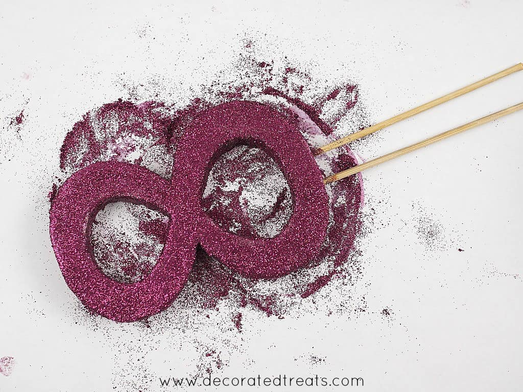 Number 8 topper on a piece of white paper with purple glitter all over it and the paper