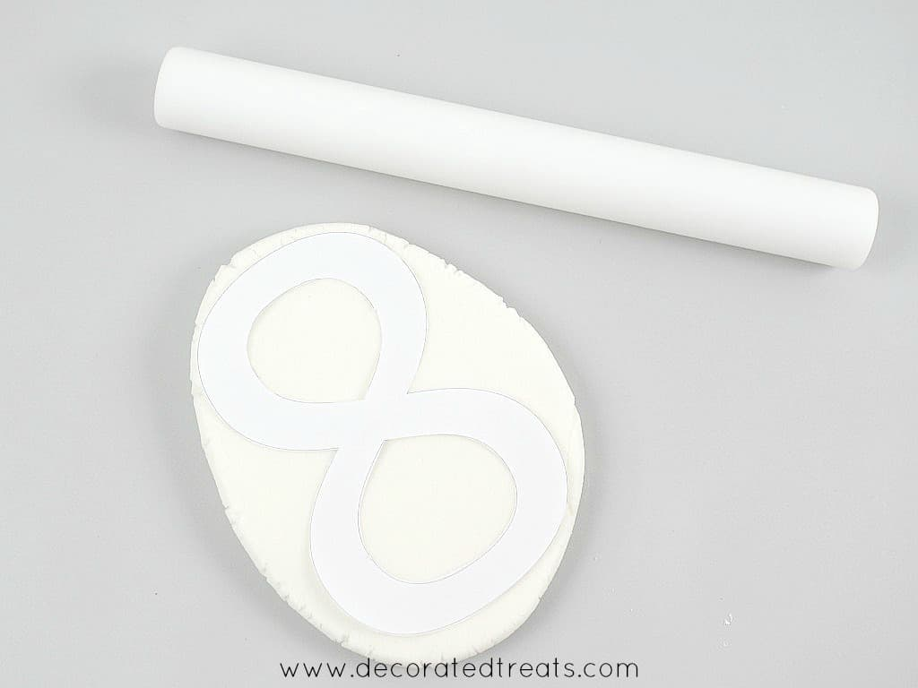 A number 8 paper template on a piece of white rolled fondant. Next to it is a white rolling pin